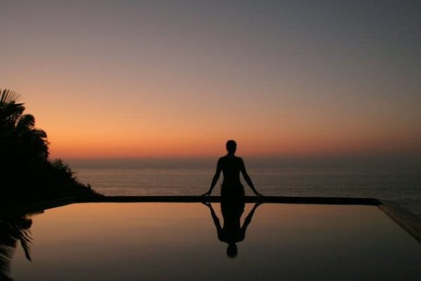 A red-hued sunset on the Pacific Ocean with a woman sitting on the edge of an infinity pool.
